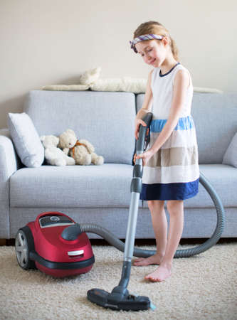 vac: Cute little girl cleaning carpet with vacuum cleaner.