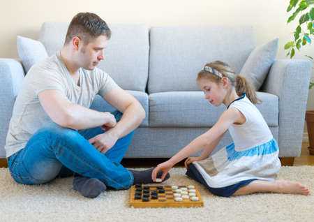 checkers: Little girl and her father playing checkers. Stock Photo
