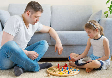 board game: Little girl and her father playing ludo.