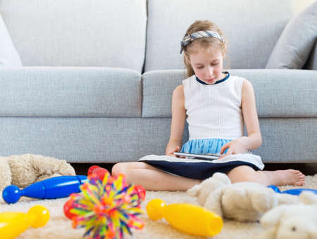 carpet clean: Its time to clean up your toys! Little girl playing with tablet pc, dont want to do the cleaning.