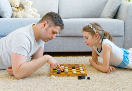Little girl and her father playing checkers. Stock Photo