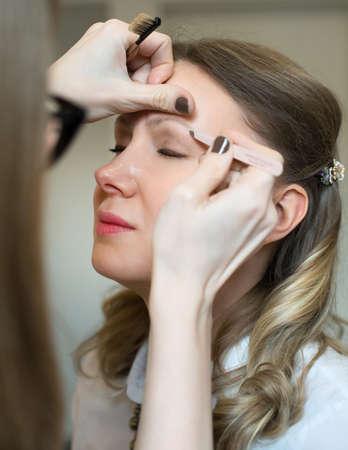 tweezing eyebrow: Make-up artist tweezing eyebrow on models face.