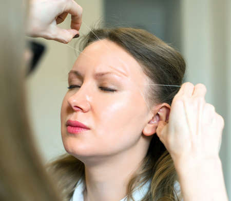 Make-up artist making eyebrow correction on models face. Фото со стока