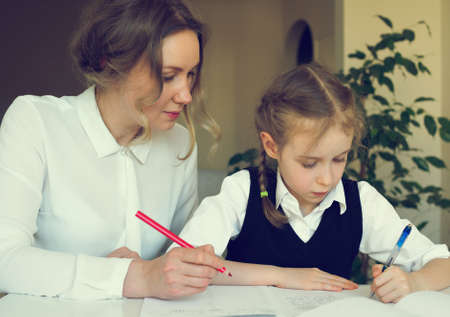mum and child: Mother helping daughter with homework at home. Vintage effect.