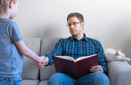 disturbing: Little girl disturbing her dad while he is reading book. Stock Photo