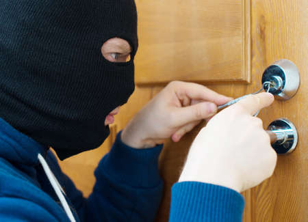 heist: Thief opening door with lock picker. Stock Photo