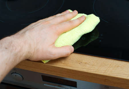 cooktop: Mans hand wipes cooktop in the kitchen.