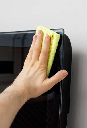 tv panel: Mans hand wipes dust from TV panel. Stock Photo