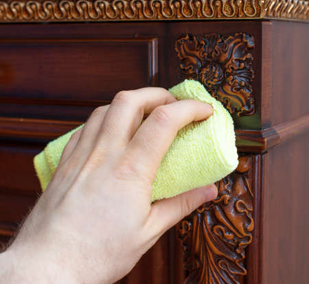 Man's hand wipes dust from antique furniture.