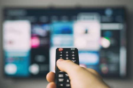 Mano masculina que sostiene el control remoto del televisor.