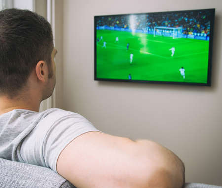 watching football: Man watching football match on television at home.