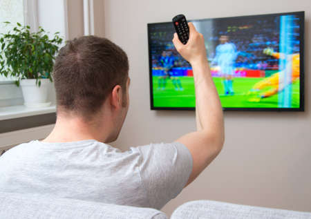 watching football: Goal! Man watching football match on television at home. Stock Photo