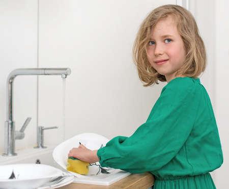 Kleines Mädchen beim Abwasch in der Küche. Standard-Bild
