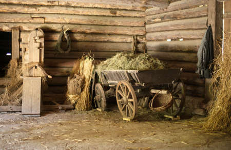 hayloft: Wooden cart with hay in old barn. Stock Photo