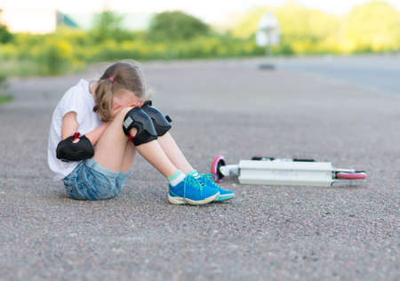kneepad: Little girl fell from the scooter on the street. Stock Photo