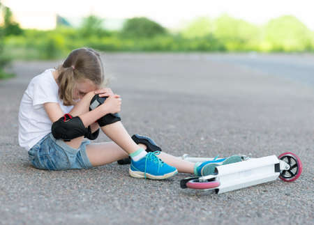 fell: Little girl fell from the scooter on the street. Stock Photo