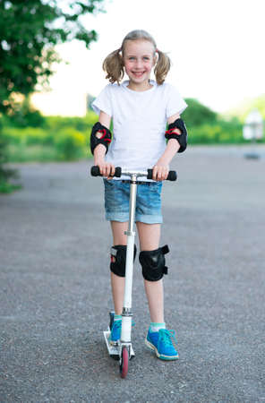 kneepad: Little girl riding scooter on the street. Stock Photo