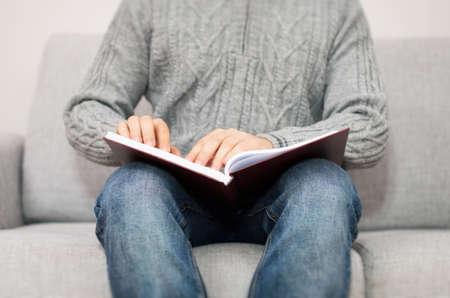 braille: ciego libro de lectura en braille en el sofá.