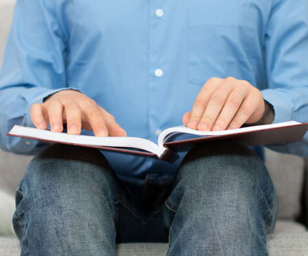 braille: Blind man reading braille book on the couch. Stock Photo