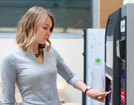 machines: Pretty woman using coffee vending machine.