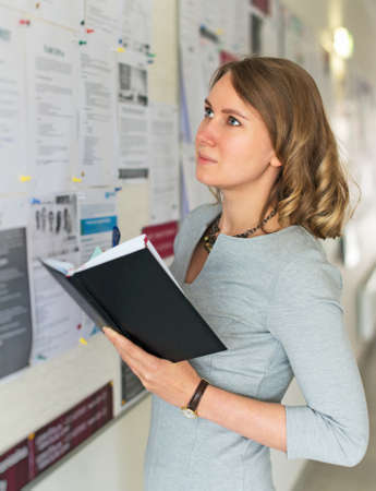 Young female student looking through job offers on board.