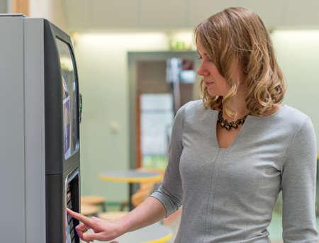 Pretty woman using coffee vending machine.