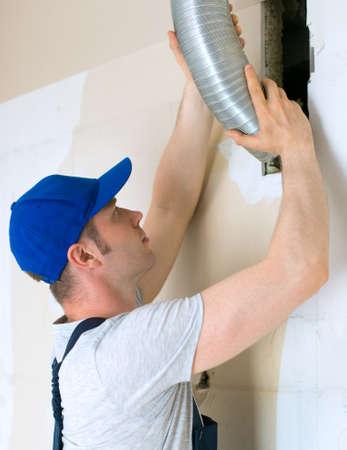 ventilate: Man setting up ventilation system indoors.