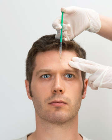 Handsome man is getting injection. Concept of aesthetic beauty. Place for your text. Stock Photo