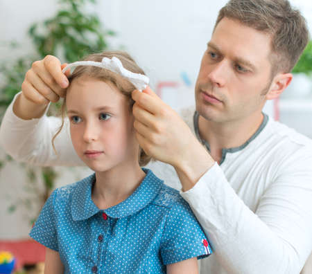 upbringing: Father styling hair of his daughter at home.
