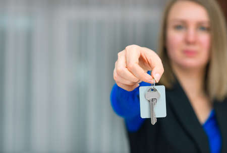 hotel receptionist: Hotel receptionist offering key from room. Place for text.