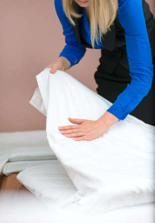 roomservice: Room service. Woman making bed in hotel room.