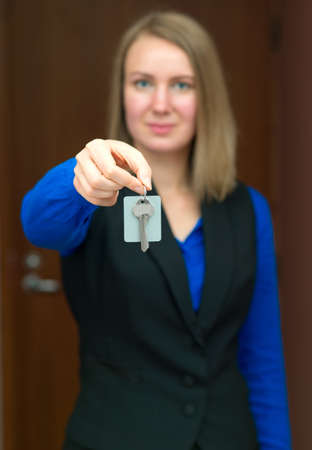 hotel receptionist: Hotel receptionist offering key from room.