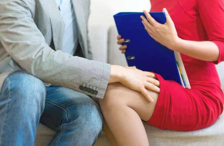 Sexuální obtěžování na pracovišti. Muž se dotýká koleno sekretářky.