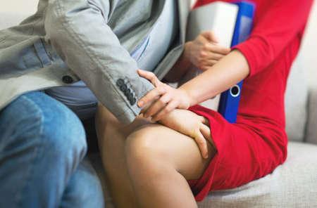 muž: Sexuální obtěžování na pracovišti. Muž se dotýká koleno sekretářky.