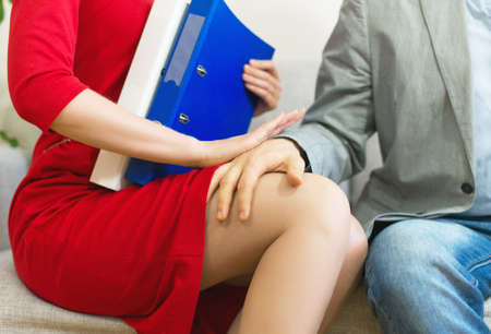 Sexual harassment at work. Man touching secretarys knee.