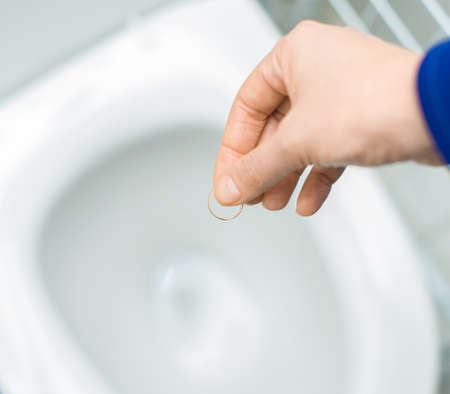 bereavement: Divorce concept. Woman throwing her wedding ring in the toilet.