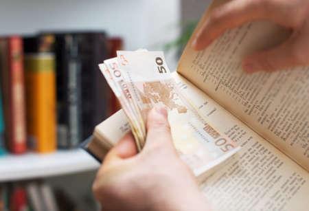 stash: Man hiding money in a book. Secret stash place. Stock Photo
