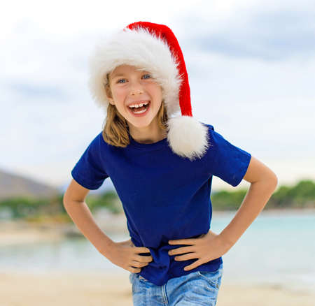 beach happy new year: Happy little girl on the beach. Christmas and new year vacations concept. Space for your text.