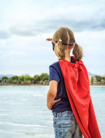 Superhero kid looking into distance.