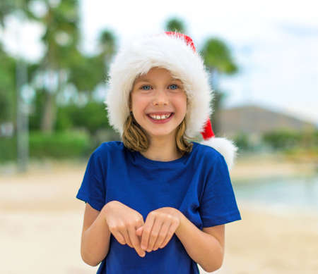 beach happy new year: Happy little girl on the beach. Christmas and new year vacations concept.