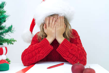 Sad little girl in red hat writing a letter to Santa Claus.