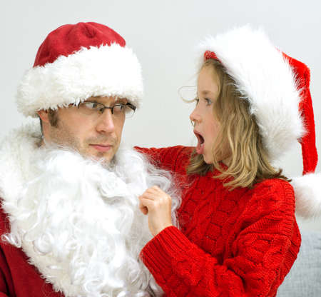 finding out: Surprised little girl looking at fake Santa Claus.