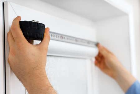 Człowiek instalowania kasety rolety na okna. Zdjęcie Seryjne