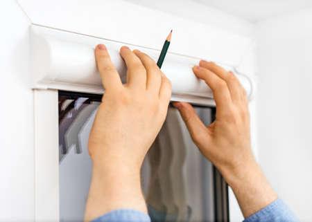 blinds: Man installing cassette roller blinds on windows. Stock Photo