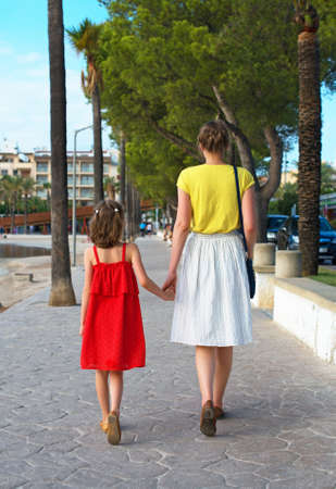 Little girl and her mother walking down the street. Stock Photo