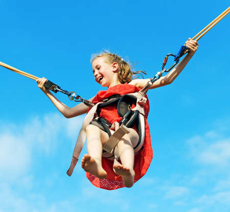 Little girl on bungee trampoline with cords. Place for text. Stock Photo