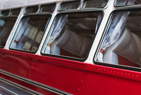 Part of red retro bus with passenger seats. Stock Photo