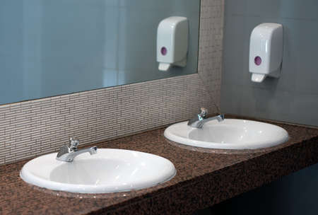Empty public toilet room with sinks and taps.