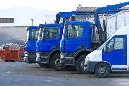 Few garbage trucks on the parking lot.