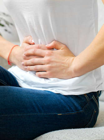 incontinence: Unrecognizable woman on the bed with stomach pain.